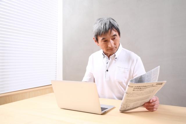 新聞片手にパソコンの前に座る中高年男性